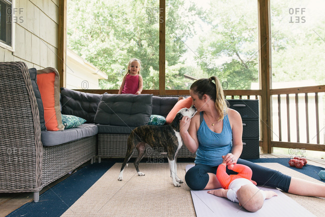 Mother after work-out with two young daughters and family dog