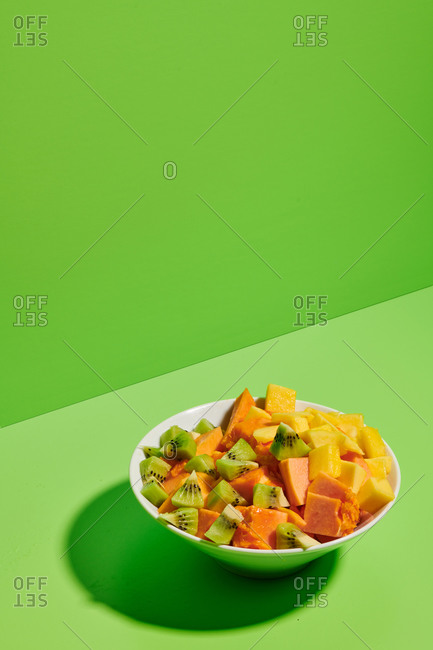 Closeup of delicious healthy natural fruit salad with chopped papaya and kiwi served in plate placed on bright green background