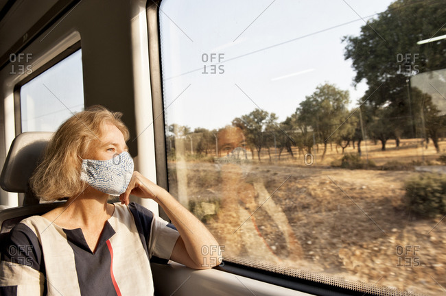 Pensive female traveler wearing protective mask sitting on comfortable passenger seat and looking out of window of train