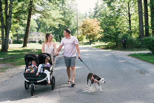 Young family walking down suburban street in stroller together