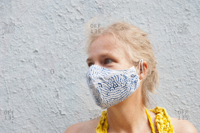 Calm middle aged female wearing protective mask standing on street near concrete building and looking away during coronavirus epidemic