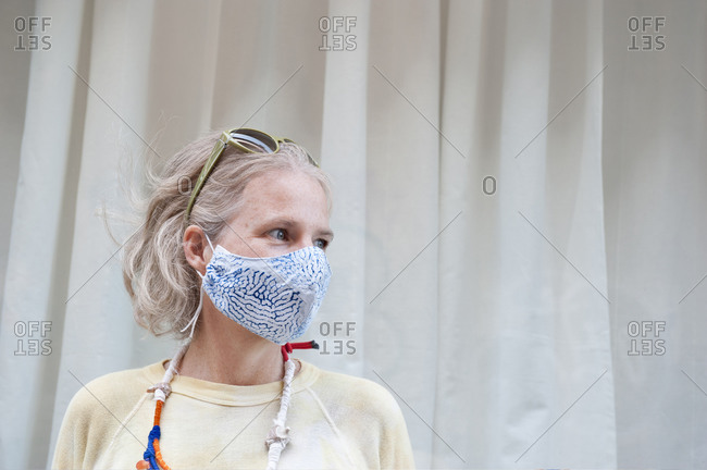 Calm middle aged female wearing protective mask standing on street and looking away during coronavirus epidemic