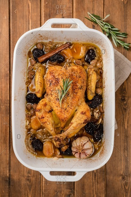 Top view of stuffed baked chicken in dish with garlic and cinnamon stick placed on wooden table
