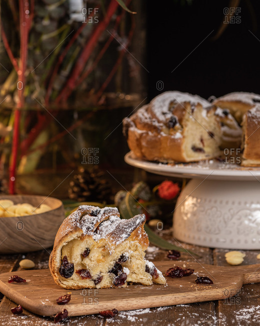 Sweet traditional Kringle with berries and powdered sugar placed on wooden table in kitchen
