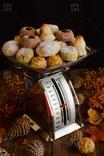 Various delicious Panellets arranged on wooden table with autumn leaves and cones prepared for celebration of All Saints Day in Spain