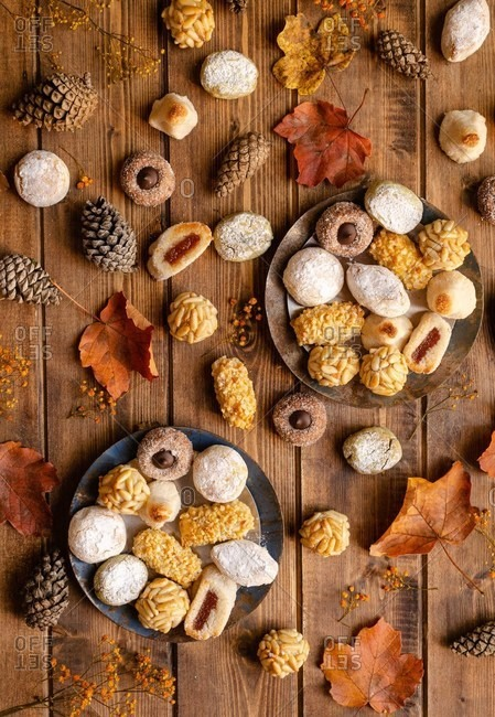 Top view of assorted tasty Panellets placed on table with dried autumn plants and cones for celebration of All Saints Day in Spain