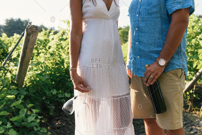 Low half crop of couple standing with wine and glasses in vineyard