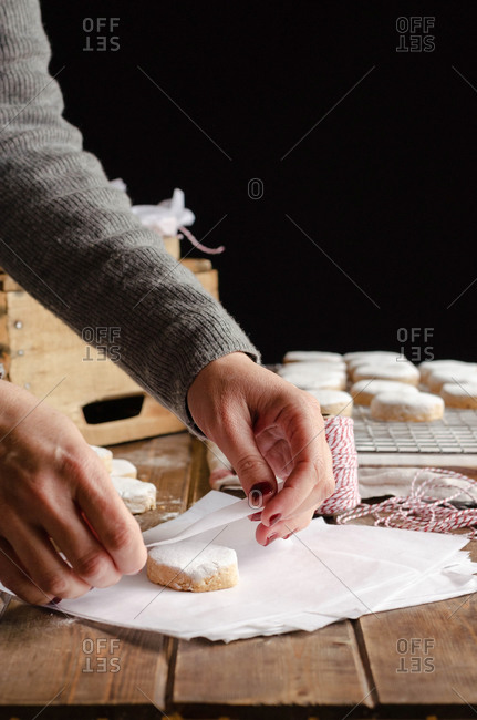 Anonymous female wrapping tasty homemade Polvorones in paper while preparing gifts for Christmas celebration