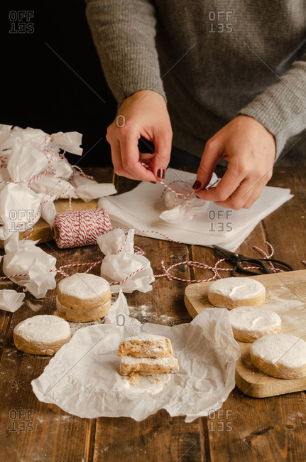 Unrecognizable female standing at wooden table and wrapping homemade delicious Polvorones in paper for celebrating Christmas