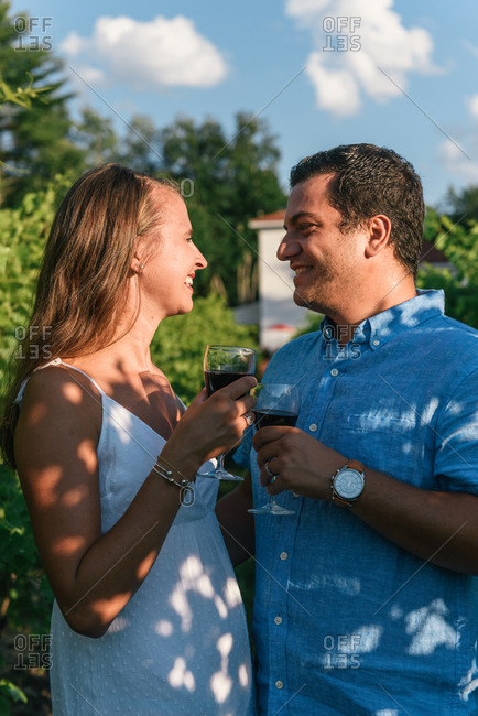 Close up of wife and husband smiling at each other with wine glasses