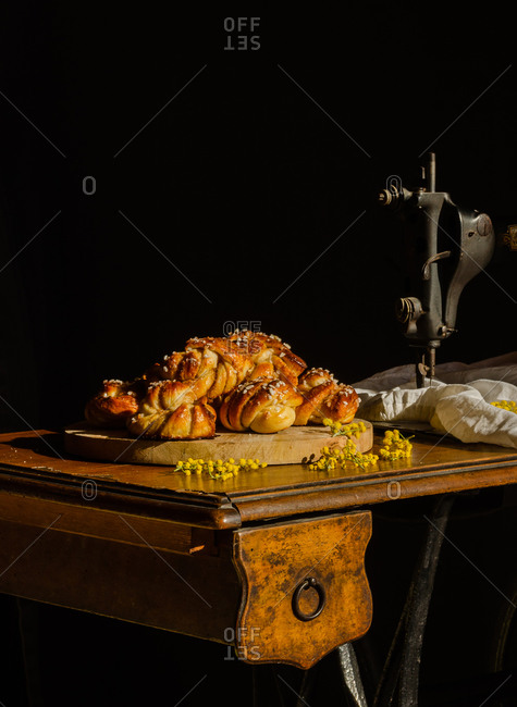Pile of delicious Swedish cardamom buns placed on cutting board on rustic table with sewing machine