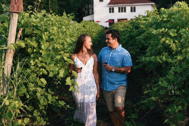 Wife and husband smiling at each other while walking out of vineyard