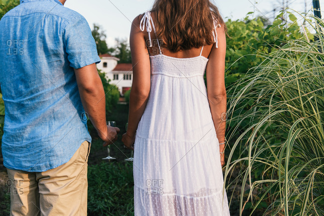 Low crop behind backs of couple holding wine glasses at vineyard