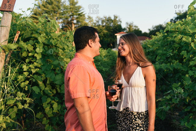 Young couple smiling at each other with wine glasses in vineyard