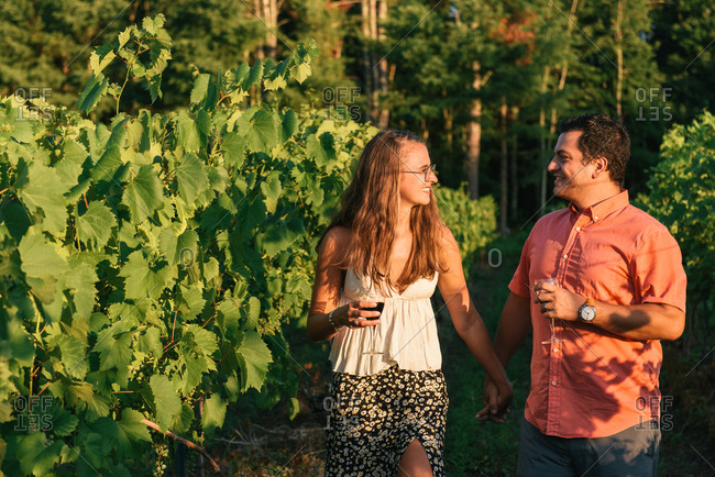 Couple looking at each other in sunset light while strolling vineyard