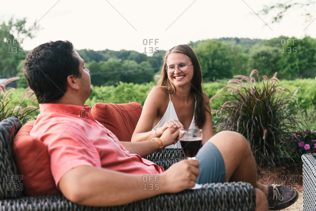 Couple lounging on rattan chairs while sipping wine around vineyard