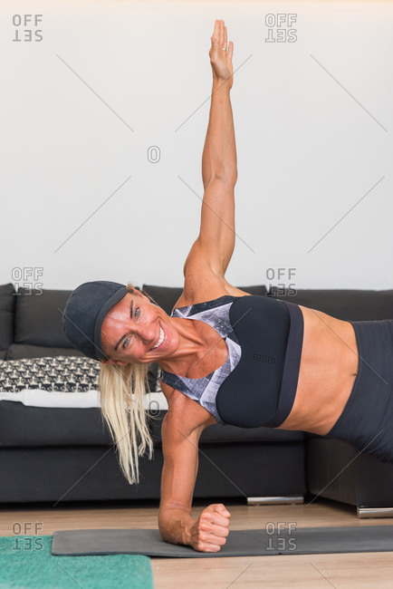Strong female athlete in sportswear doing side plank exercise while smiling and training at home