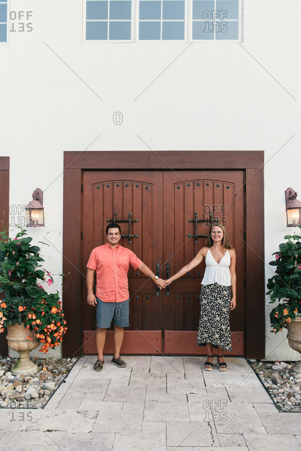 Young couple standing with hands held apart in front of winery doors