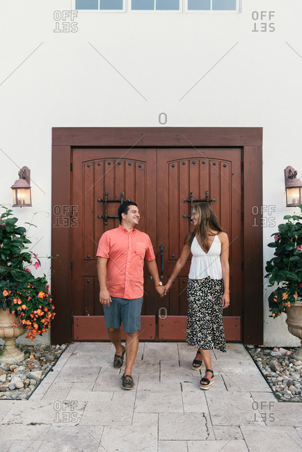 Couple walking forward and laughing in front of ornate doors