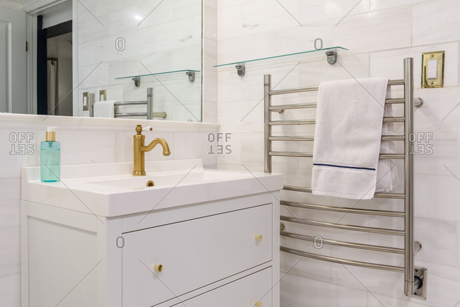 Corner view of luxury bathroom sink with towel warmer