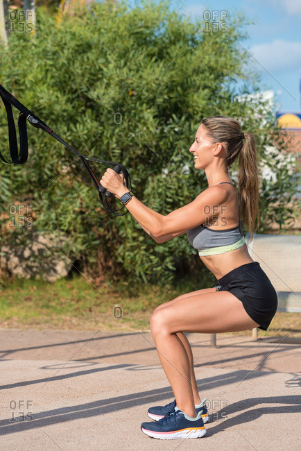 Side view of smiling female athlete doing squats with straps during workout in summer