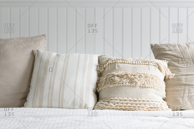 A collection of white and cream pillows on a bed with wood headboard