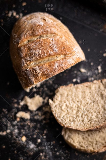 Detail of freshly baked homemade bread on black and wooden background,