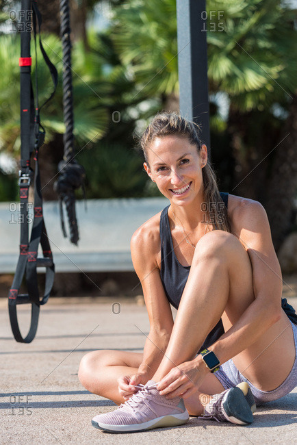 Muscular female athlete sitting on sports ground and tying shoelaces on sneakers while looking at camera before training