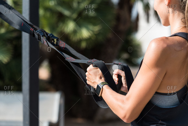 Cropped unrecognizable smiling female athlete doing squats with straps during workout in summer