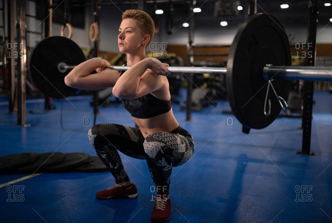 Sportswoman doing clean and jerk exercise during workout