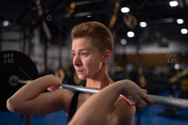 Concentrated female athlete doing clean and jerk exercise