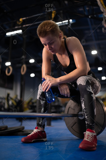Exhausted sportswoman drinking water on barbell