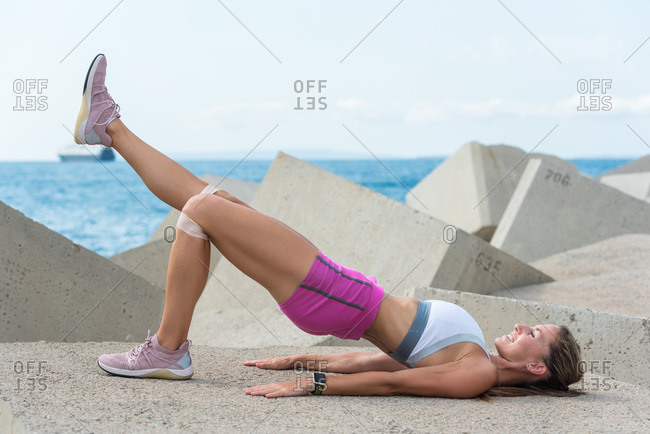 Side view of athletic female with strong body doing bridge exercise with elastic band on sea breakwater in summer
