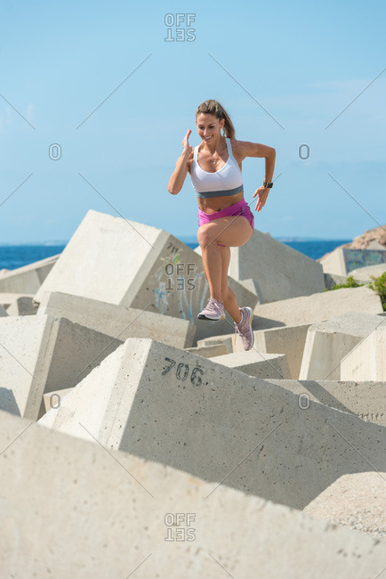 Muscular sportswoman running on stone of breakwater while training near sea on sunny day