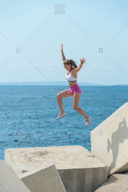 Side view of strong female athlete in sportswear in moment of jumping on breakwater boulders during training at seaside in summer