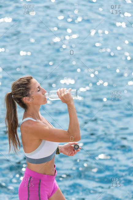 Side view of thirsty female athlete standing near sea and enjoying fresh water after workout in summer