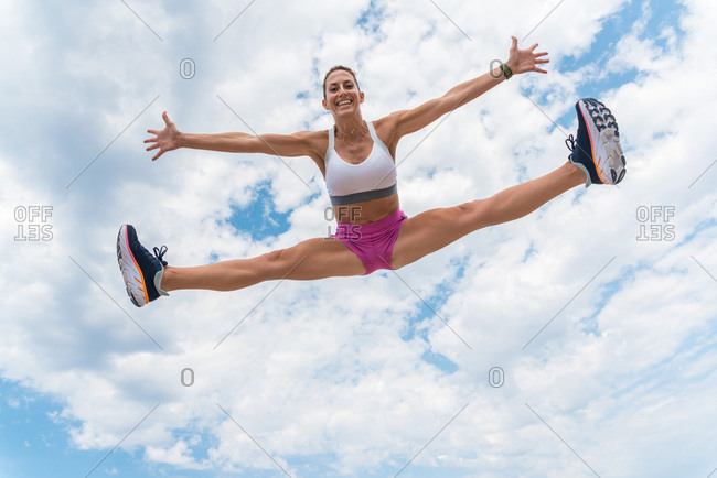 From below of strong female athlete in moment of jumping with splits and outstretched arms during workout on background of cloudy sky