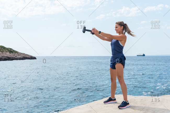 Strong female in sportswear doing exercises with dumbbell while standing on stone quay near sea and looking away