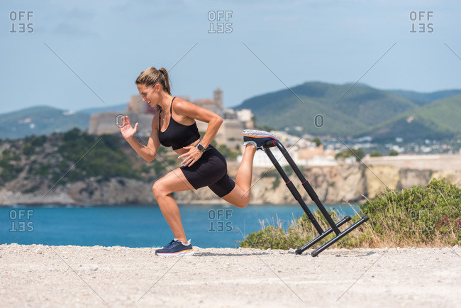Side view of determined sportswoman in activewear doing squats during training while using metal railing