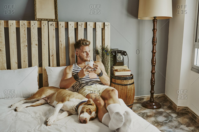 A young blond boy with a cup of coffee and his dog in bed
