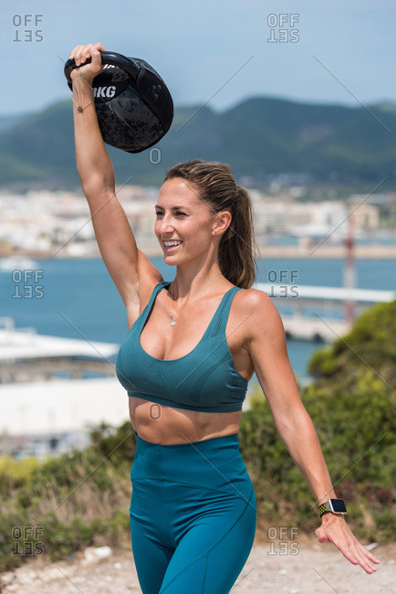 Muscular female athlete in bra and leggings lifting heavy kettlebell while training on sunny day and looking away