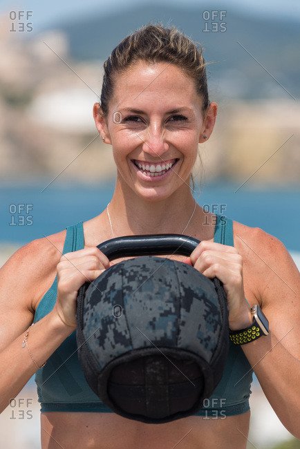 Muscular female athlete in bra and leggings lifting heavy kettlebell while training on sunny day and looking at camera