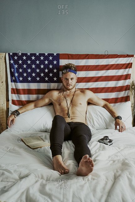 A young man in bed looking at the camera with the American flag