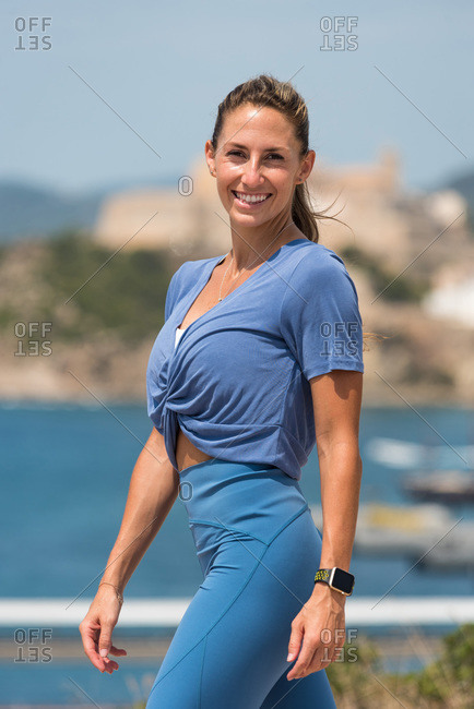 Determined female athlete with strong body in sportswear standing on background of sea and looking at camera