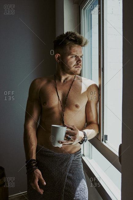 A young man with a bath towel looks out the window while drinking a coffee