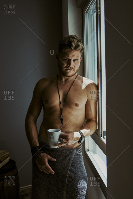 A young man with a bath towel looks at the camera while drinking a coffee