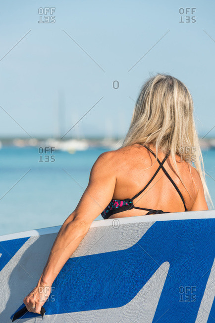 Back view of anonymous slim female surfer walking in sea with paddle board on sunny day in summer