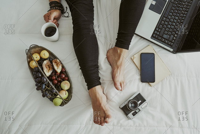 Feet and legs of a man in bed next to a computer, fruit, coffee, camera and a mobile phone