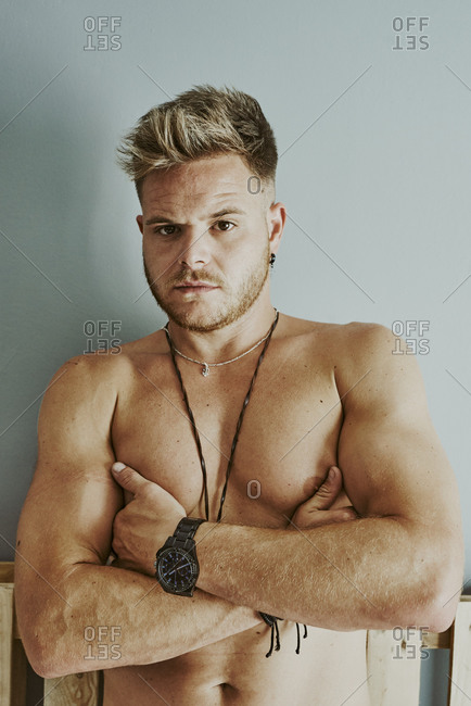 A young man with no shirt is standing with his arms crossed looking at the camera