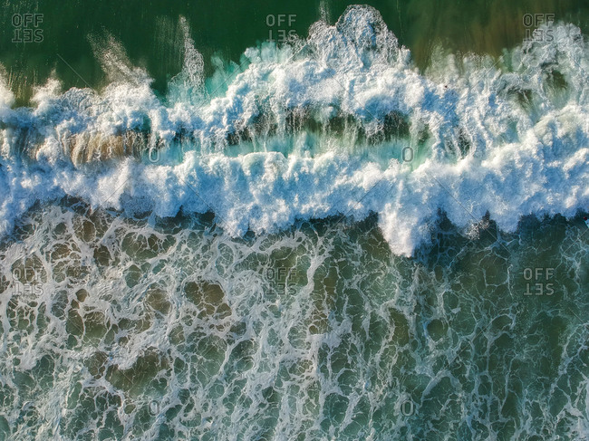 Aerial view from a big wave crashing in a beach. Drone view